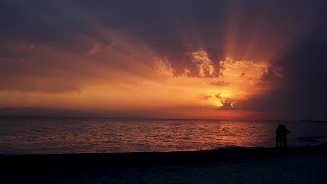 vidéos et rushes de bonne personne et un beau coucher de soleil sont suffisants pour terminer la journée parfaite. silhouette de l'homme et de la femme dans l'amour. - être debout