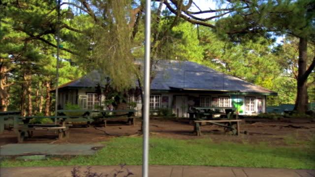 vidéos et rushes de angled driving by unidentified large house w/ picnic tables in yard. - table de pique nique