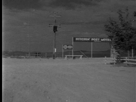 stockvideo's en b-roll-footage met approaching 'hitchin' post motel' tall sign turning right into drive amp up toward office w/ 'vacancy' amp 'aaa approved' signs on brick cloumn car... - 1952