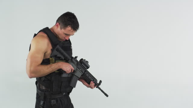 Right side shot of soldier slowly turning toward camera. Shot in slow motion against a grey screen.