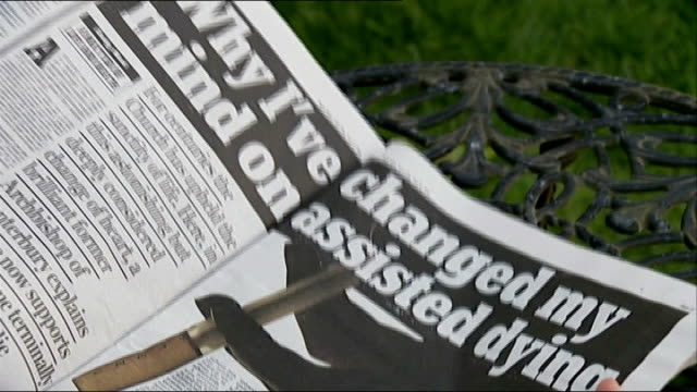 lord carey backs assisted suicide bill ext jane nicklinson taking seat in garden with newspaper newspaper opened to article by lord carey on assisted... - article stock videos & royalty-free footage
