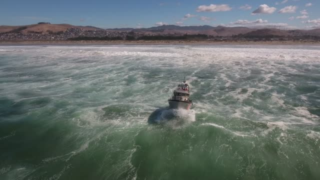 Right to left front coast guard over wave, rough seas, rouge wave crashing over boat agitated water, Drone aerial video, 4k, rescue, marine, pacific, tide, surge, danger, dangerous waves raw .mov
