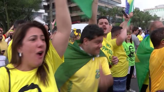 rightwing candidate jair bolsonaro wins election brazil rio de janeiro ext people in brazilian political shirts cheering and shouting pan reporter to... - election stock videos & royalty-free footage