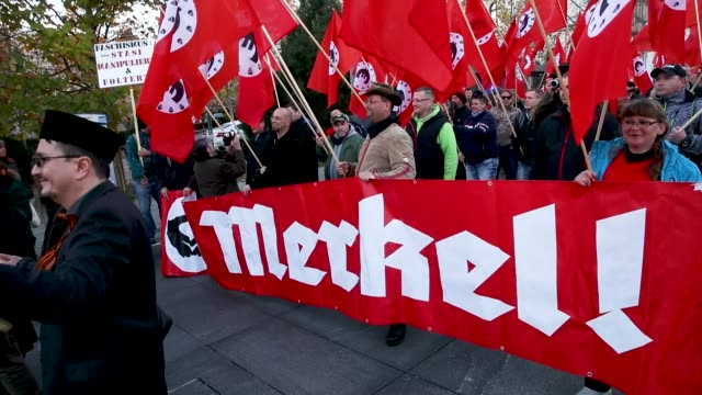 right-wing protesters carry a satirical banner in mock-support of german chancellor angela merkel on the day she visited the city on november 16,... - satire stock-videos und b-roll-filmmaterial