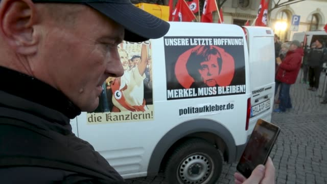 vídeos de stock e filmes b-roll de rightwing protesters prepare to march with satirical banners flags and signs in mocksupport of german chancellor angela merkel on the day she visited... - sátira