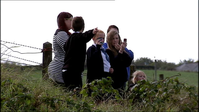 rihanna told off by farmer during filming of her latest video; northern ireland: county down: ext hay field youngters filming on phones rihanna... - ulster county stock videos & royalty-free footage