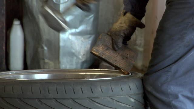 cu rim being bent by mechanic into place / los angeles, california, usa  - 中年の男性だけ点の映像素材/bロール