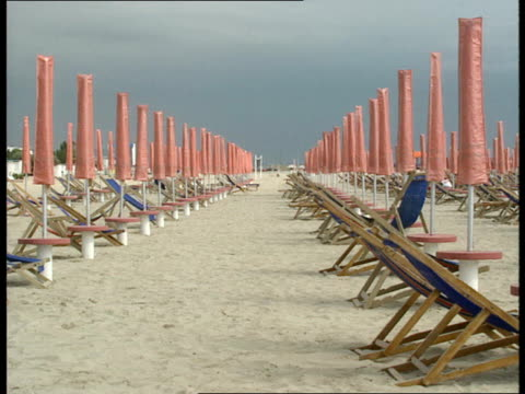 rimini beach 'slime' cr757 rimini ext gvs of near deserted beach deckchairs and sun loungers umbrellas folded up with few sunbathers and swimmers/... - folded stock videos and b-roll footage