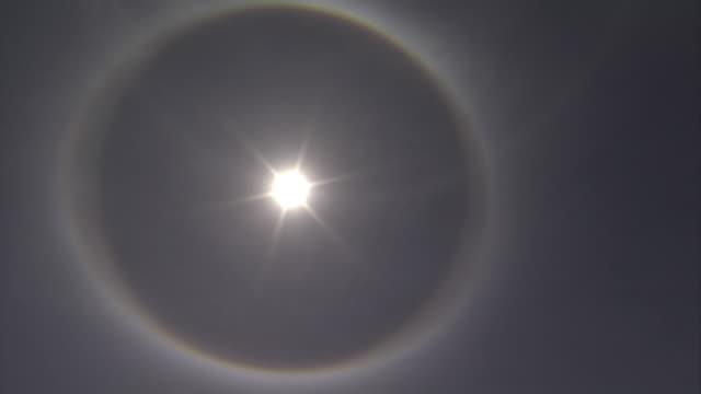 vídeos de stock, filmes e b-roll de a ring forms in the haze around the sun. available in hd. - símbolo conceitual