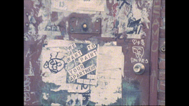 Rings doorbell at JeanMichel Basquiat's studio on Great Jones Street in downtown New York / zoom in to graffiti and posters covering the door and...