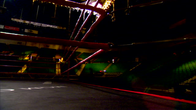 ringside pan boxing ring in soft light overhead spots off lighted girder amp follow spot on - ボクシングリング点の映像素材/bロール