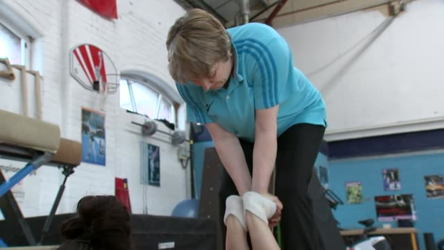 British gymnast Claudia Fragapane Fragapane putting grips onto wrists and with head resting on hands in gym Coach pushing down on Fragapane's feet...