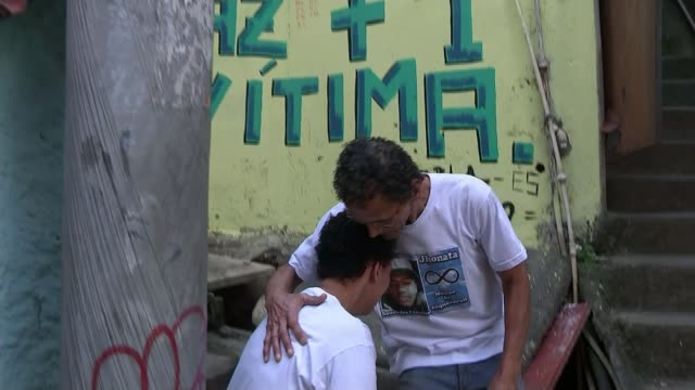 Rise in crime levels in Rio de Janeiro BRAZIL Rio de Janeiro EXT Grandfather comforting crying mother of boy shot by police at scene of shooting...