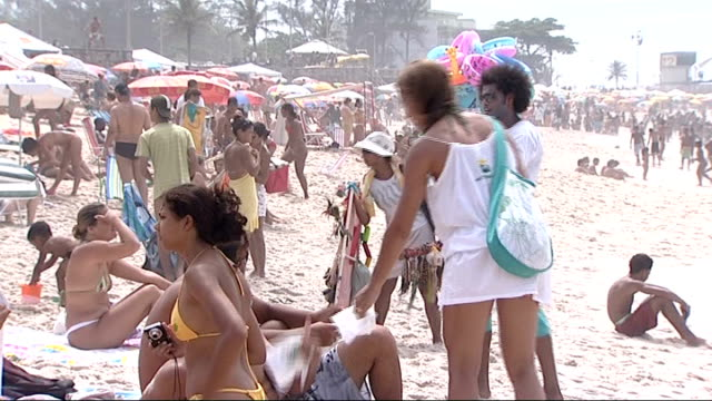 vidéos et rushes de rio de janeiro ext shot of two women in bikinis looking out to sea / close up of people on beach / shot from crowded beach out to sea / close up of... - vendeur ambulant