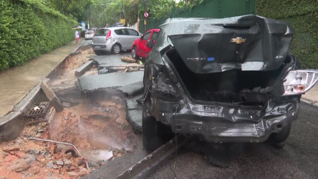 vídeos y material grabado en eventos de stock de rio de janeiro residents walk by cars damaged by torrential rain as city workers try to clean the streets of the rubbles left by flash floods that... - destrucción