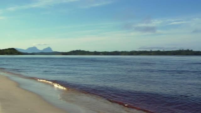 stockvideo's en b-roll-footage met ws pan rio negro and fluvial beach, sleeping beauty mountain range in background / sao gabriel da cachoeira, amazonas, brazil - color negro