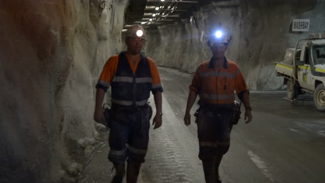 rio tinto miners walk along a decline passage 600 metres below ground level at rio tinto's block cave mine / rio tinto miners walk along a decline... - mine stock videos & royalty-free footage