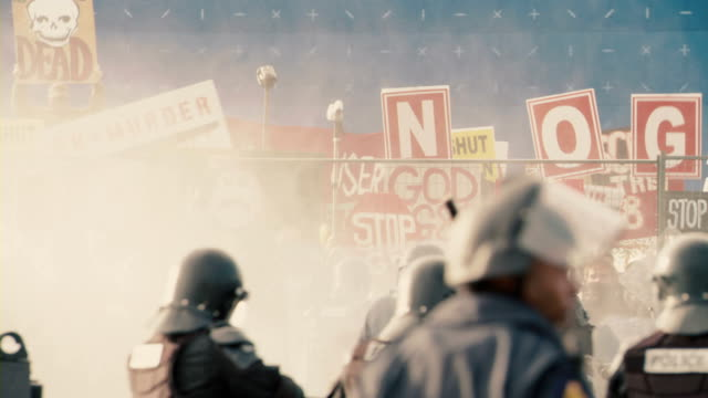 riot cops advance on protestors while spraying water with a pressurized hose. - placard stock videos & royalty-free footage