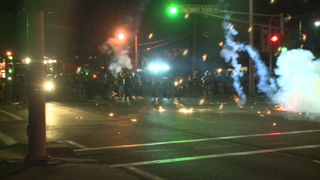 vídeos de stock e filmes b-roll de ktvi riot police and military shoot tear gas into the street to deter rioters on august 13 2014 in ferguson missouri protests and riots broke out in... - missouri
