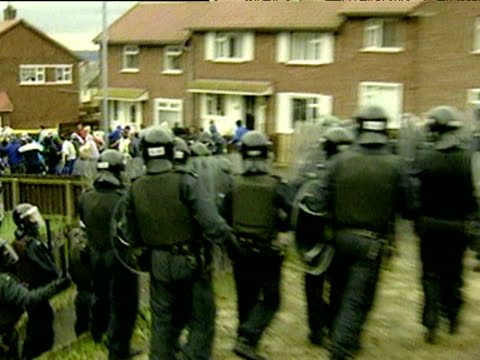 vídeos de stock e filmes b-roll de riot police charge at loyalist rioters throwing stones as catholic families walk children to holy cross primary school belfast 5 sep 01 - belfast