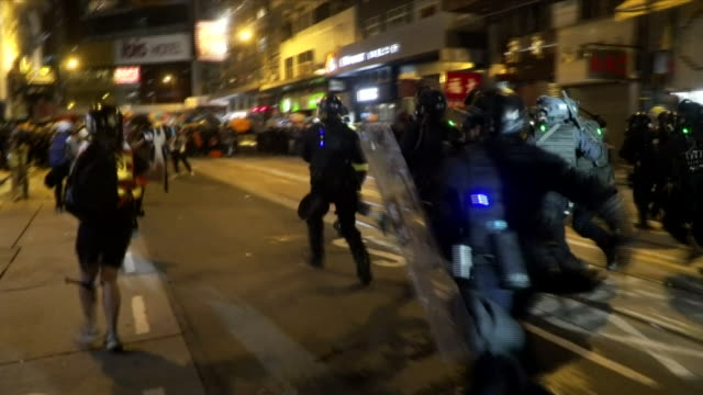 riot police charging and firing at protesters in hong kong - demonstrant stock-videos und b-roll-filmmaterial
