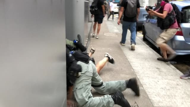 riot police clash with protesters and use crowd control measures while a member of the media washes his eyes with solution as protests return to hong... - hong kong stock videos & royalty-free footage