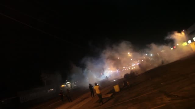 Riot police fire tear gas and flashbangs at protesters in Ferguson Mo as they approach the Target Protesters retreated back footage includes visual...