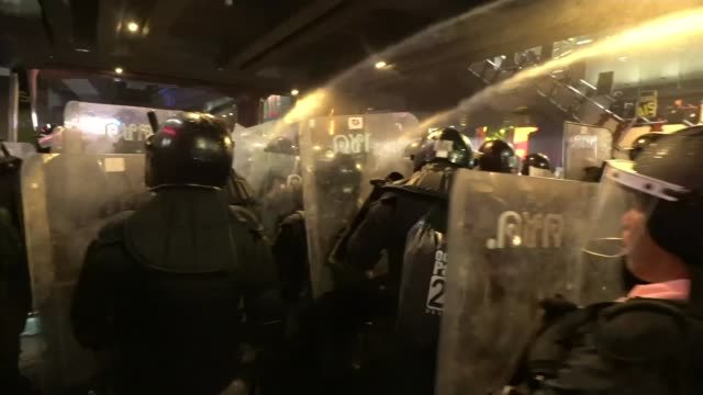 riot police fire water cannon and charge at protesters in bangkok; thailand: bangkok: ext / night reporter to camera sot as alongside riot police. - thailand stock videos & royalty-free footage
