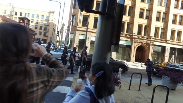 riot police move in to confront groups celebrating the win of president elect joe biden near the bradbury building in downtown los angeles. - los angeles police department stock videos & royalty-free footage