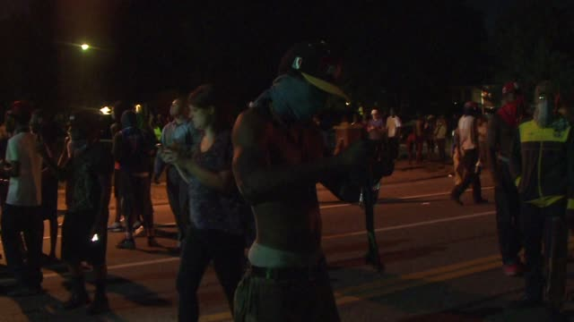 ktvi riot police throw tear gas as protesters run away shouting in ferguson mo in the wake of the shooting of michael brown - st. louis missouri stock videos & royalty-free footage