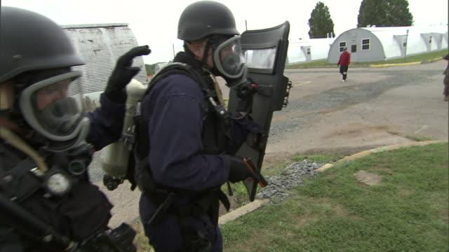 riot police walk single file onto a military base. - barracks stock videos & royalty-free footage