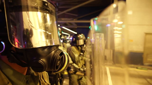 riot police wearing breathing masks fire tear gas at anti government protesters in hong kong - hong kong international airport stock videos & royalty-free footage