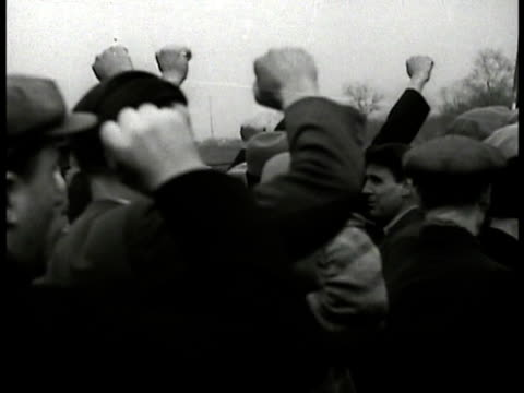 vidéos et rushes de riot size crowd in street people standing on building ledge group of people w/ raised fists large crowd standing in park setting applauding... - 1934