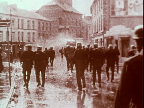 riots between roman catholics and protestants in northern ireland aug 1969 / police wearing helmets wielding clubs and riot shields running through... - 北アイルランド点の映像素材/bロール