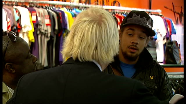 stockvideo's en b-roll-footage met boris johnson visits peckham int general views johnson speaking with peckham residents in clothes shop / young black man telling johnson of his... - peckham