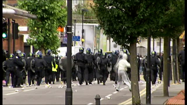 vidéos et rushes de riots in london for third night running; hackney: ext bv riot police running along street as hooded youth throws missile at them car on fire in... - hackney