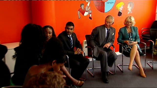 Prince Charles visits Prince's Trust centre More young people talking in group / Woman saying she cancelled her holiday to be there because she...