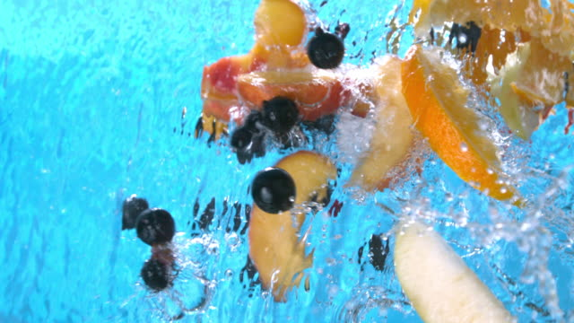 vídeos de stock e filmes b-roll de ripe fruits peach slices orange black currant apple falling into water splash cascade in slow motion shot at 1500 fps - borrifo