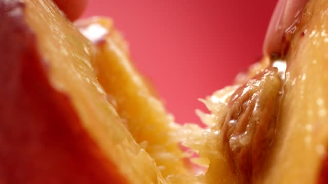 vídeos de stock e filmes b-roll de ripe, juicy peach split in half. extreme close up - fatia