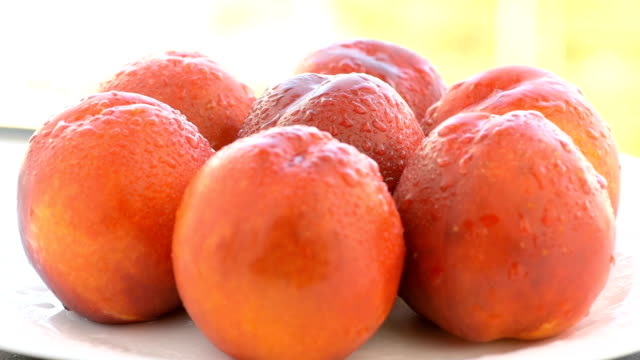 Ripe peaches on the white plate