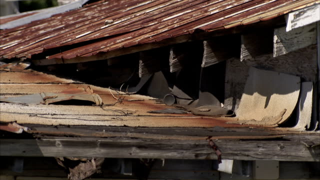 ripped up shingles lie on the roof of an old garage. available in hd. - rusty stock videos & royalty-free footage