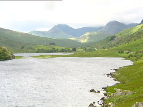 rippling waters of lake between grassy slopes of valley mountains in background under cloudy sky - snowdonia stock videos & royalty-free footage