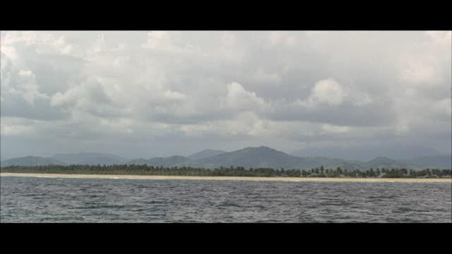 vídeos de stock, filmes e b-roll de ws ripply sea to wide beach and hilly island - formato letterbox