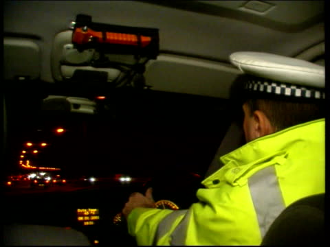 rise in drink driving figures lib police officer driving patrol car along man blowing into breathalyser held by police officer - alkoholtest stock-videos und b-roll-filmmaterial