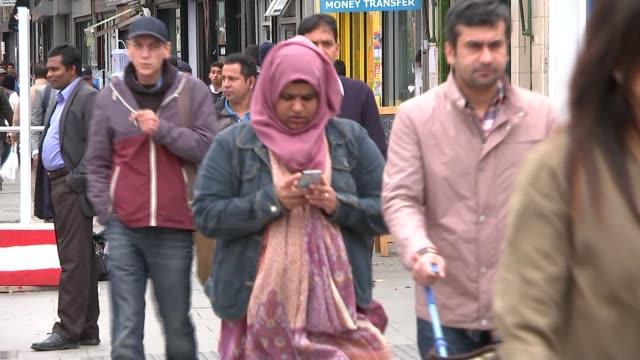 rise in islamophobia in london; england: london: ext members of muslim community along on street muslim man along muslim woman in hijab along group... - 僧衣点の映像素材/bロール
