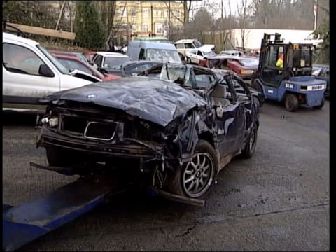 rise in number of young people caught itn england hertfordshire ext wreckage of bmw car towed towards in scrapyard side flattened car on tow truck in... - tow truck driver stock videos and b-roll footage