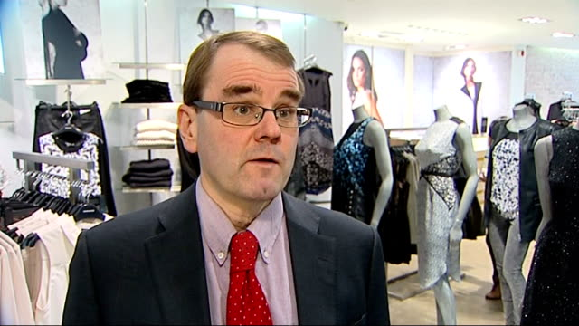 Rise in shoppers 'showrooming' and buying goods online INT Rob Skinner through clothing shop with reporter and interview SOT DVD films on display in...