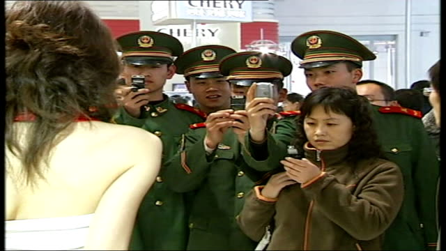 beijing beiking motor show int chinese soldiers taking photograph of model on their mobile phones at motor show model stands next to car crowds... - soldat stock-videos und b-roll-filmmaterial