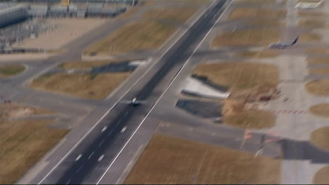 rise of drones lib view aerial of plane taxiing on runway at airport gv of airport with planes parked - ヒースロー空港点の映像素材/bロール