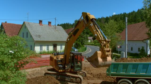 vídeos y material grabado en eventos de stock de aéreo sobre el emplazamiento de la obra donde una excavadora está cargando un camión con tierra - vehículo comercial terrestre